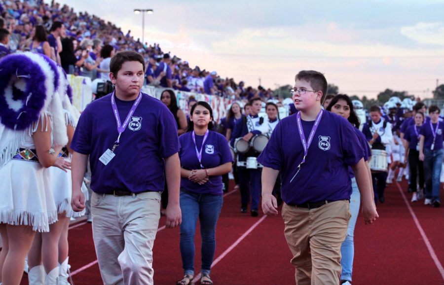 Members of the Criminal Justice program lead the Purple Pride drumline and the varsity football team onto the track toward the run-through banner during the season-opening game with Silsbee. Club members do this each home game.