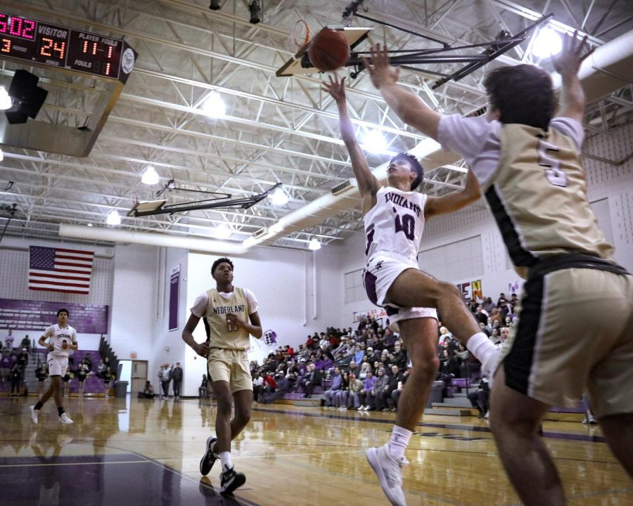 Varsity basketball player Noah Marchak floats the ball toward the basket after driving through the defense during the game with Nederland on Jan. 7, 2020 in the competition gym.