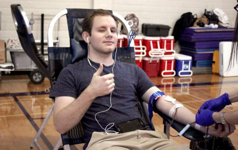 Graduate Mason Beard sits for annual NHS blood drive last year in the girls gym. This year's blood drive will be held Tuesday, Jan. 21.