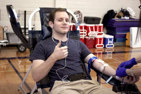 Graduate Mason Beard sits for annual NHS blood drive last year in the girls gym. This year