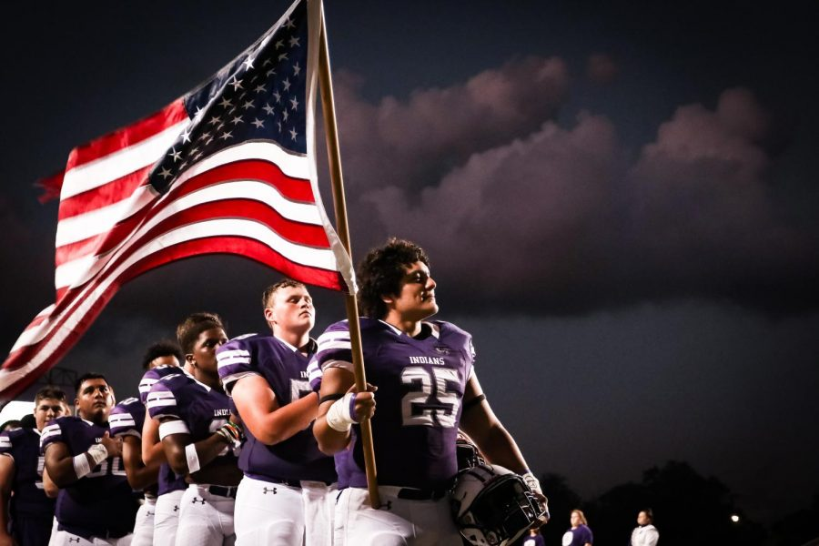 Santiago Aguadelo, senior, holds the U.S. flag as the national anthem is performed before the start of PN-Gs home football game with Tomball on Friday, Sept. 13, 2019 at Indian Stadium.