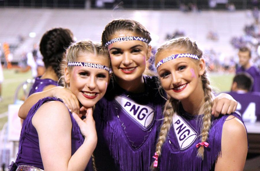 Varsity cheerleaders Hannah James, Madison Pearson and Abby Reeves smile during the Indians' home game with Dayton on Oct. 18, 2019.