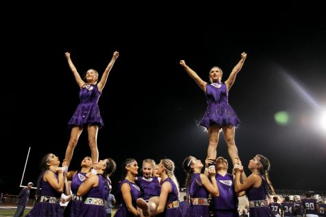 The varsity cheer team performs stunts during the Indians