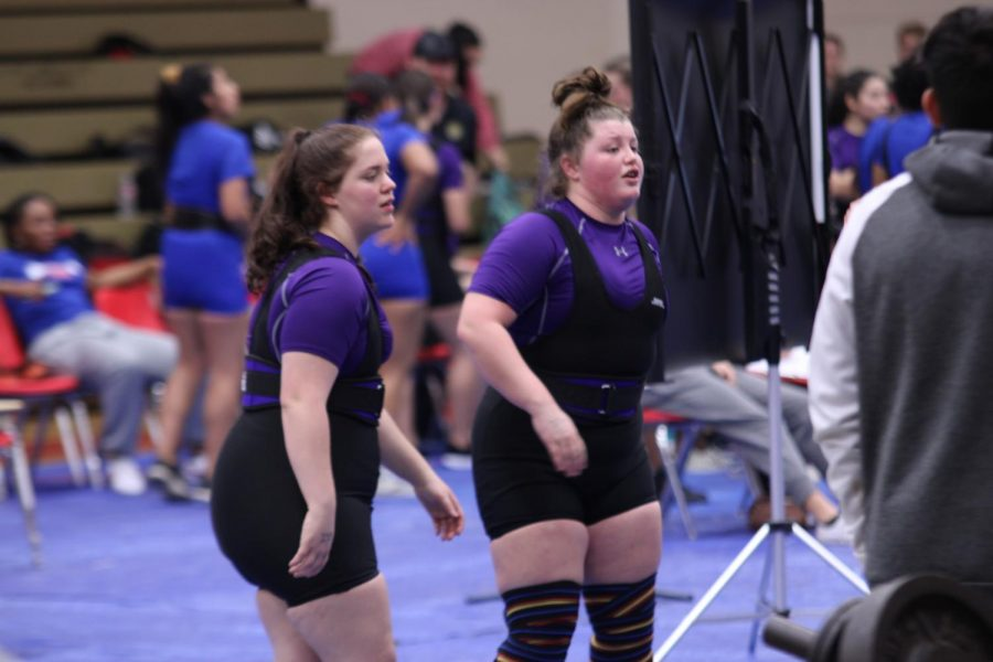From left, Savannah Roberts, senior and Brynleigh  Curtis observe the competition between events during last week's powerlifting meet at Bridge City.