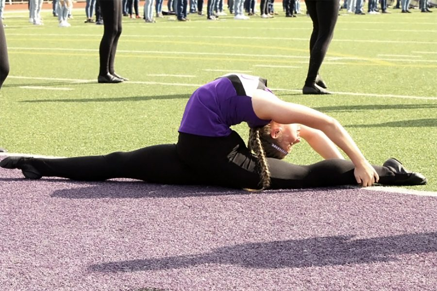 Indianette Peyton Hudgins, sophomore, stretches near the end zone as the squad waits before the start of the Dayton pep rally on Friday, Oct. 30.