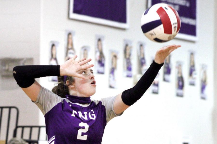 Varsity volleyball player Trista Hughes, junior, focuses intently on the ball in the act of serving toward Crosby during the Rock-A-Noos' home match in the competition gym on Saturday, Oct. 17.