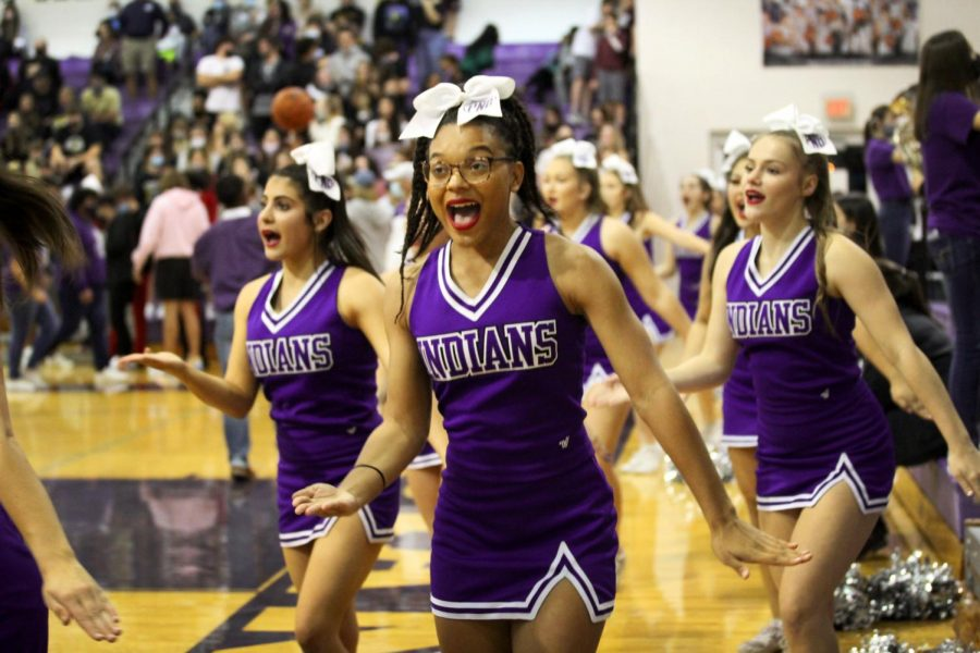 The varsity cheerleaders perform the fight song routine as the band plays